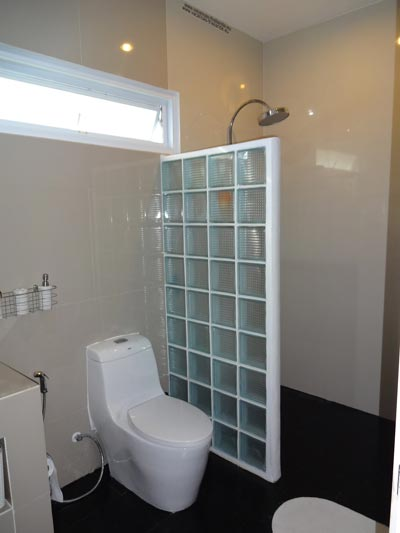 bathroom with a large Italian shower, sink, and toilet right next to the two bedrooms